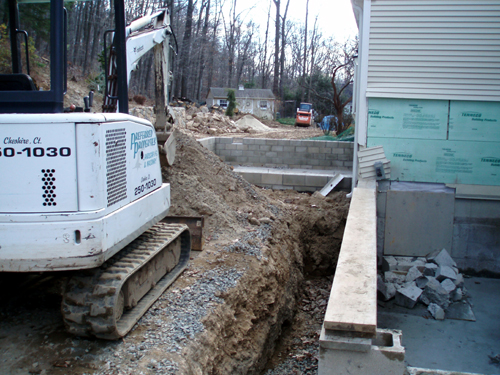 Drainage behind walls to relieve hydraulic pressure off the hardscapes, Gutter downspout tie ins, Gutter leads into an infiltrator, Complex tie ins including perimeter of foundation